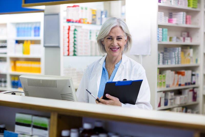 Le apotekaren som rymmer en skrivplatta i apotek royaltyfri fotografi