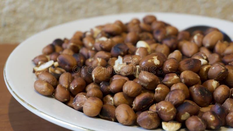 Le arachidi arrostite fanno un spuntino in piatto bianco negli ambiti di provenienza di legno - primo piano di American National  immagini stock libere da diritti