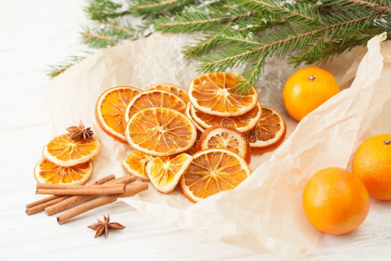 Le arance ed i bastoni di cannella secchi con abete innevato si ramificano immagini stock libere da diritti