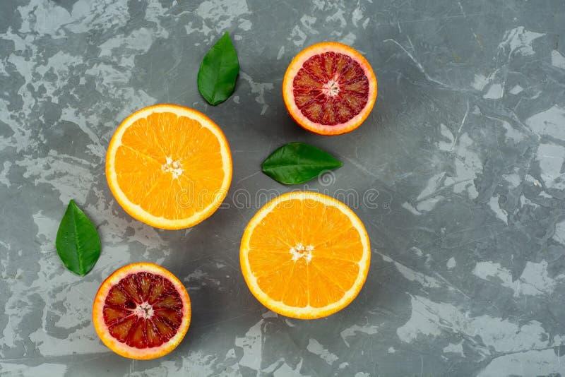 Le arance fruttifica composizione con le foglie verdi e fetta su fondo concreto, vista superiore immagini stock libere da diritti