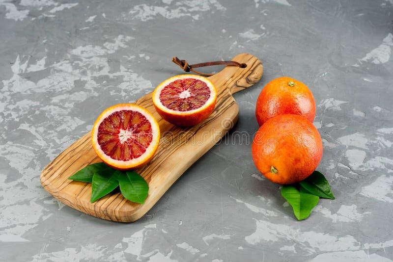 Le arance sanguinelle siciliane succose mature affettate ed intere fruttifica sopra il fondo concreto di struttura Vista superior fotografie stock libere da diritti