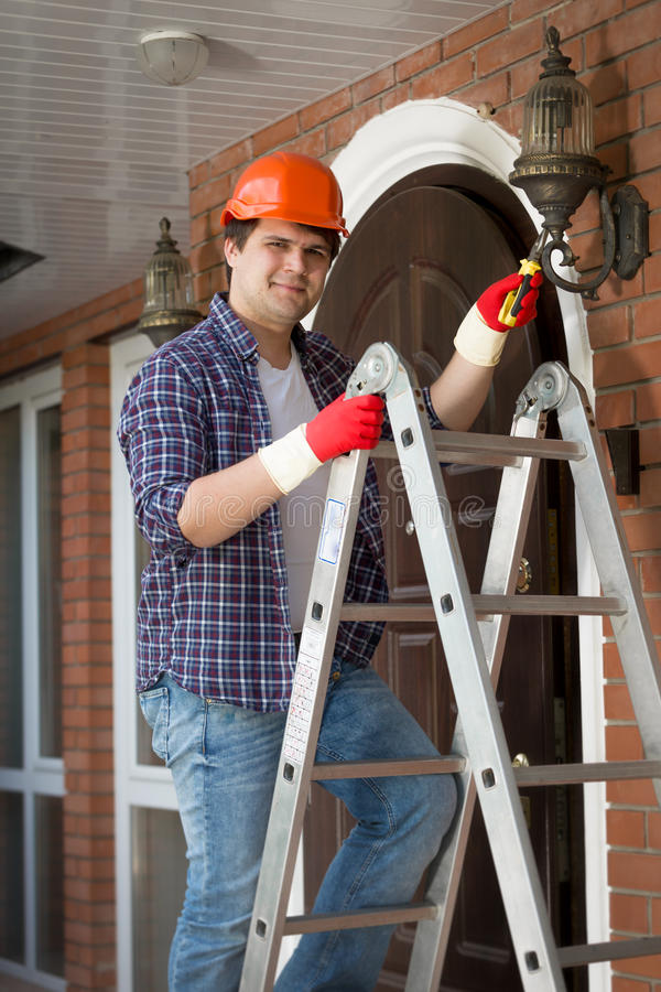 Le arbetaren i hardhat som reparerar den utomhus- lampan på huset royaltyfri foto