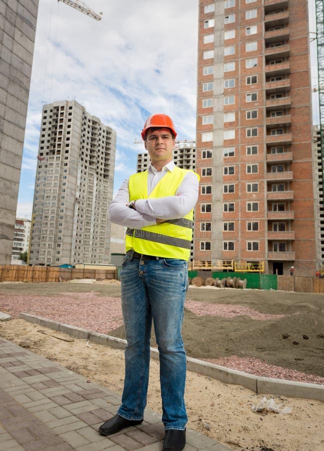 Le arbetaren i hjälm och säkerhetsvästanseende på byggnadssi royaltyfri bild