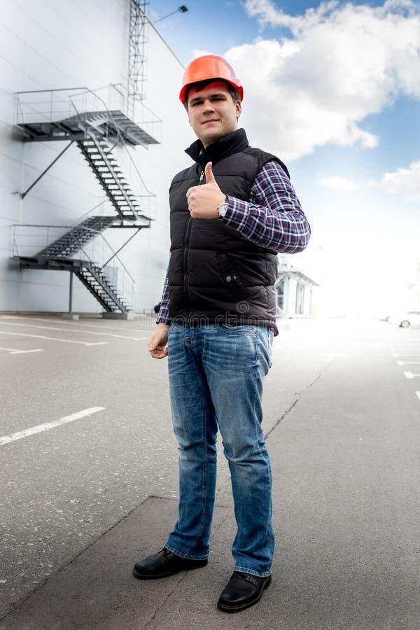 Le arbetaren i visningtumme för hård hatt upp på byggnadsplats arkivfoto