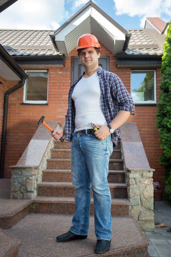 Le arbetaren som framme poserar av hus med stentrappuppgången arkivfoton