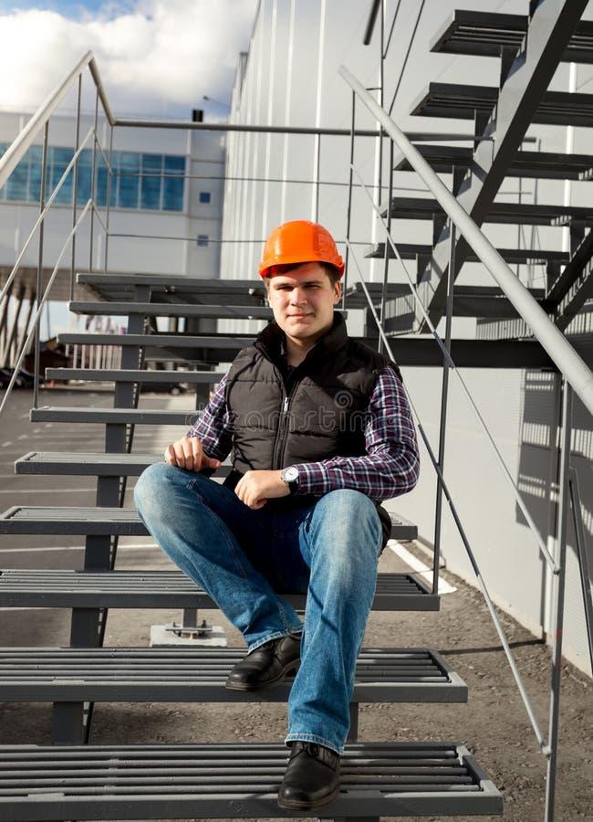 Le arbetaren som kopplar av på metalltrappuppgång under avbrott arkivfoton