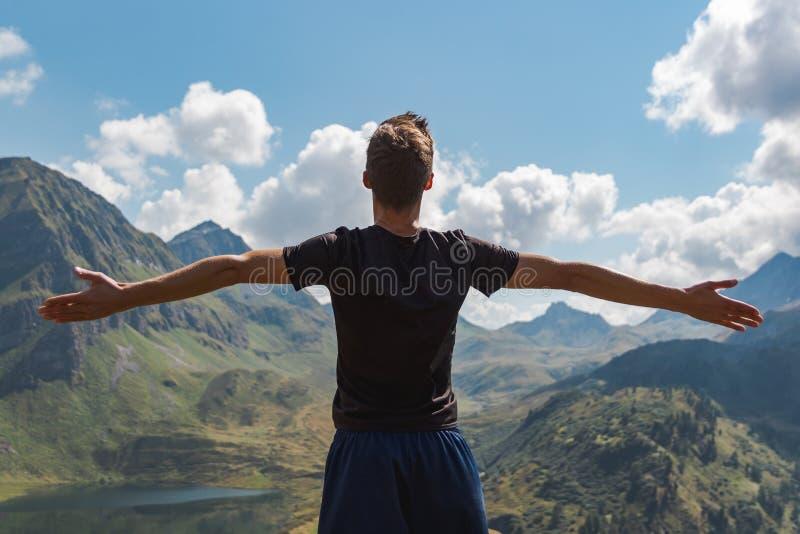 Le armi del giovane hanno sollevato godere della libertà nelle montagne durante il giorno soleggiato immagini stock