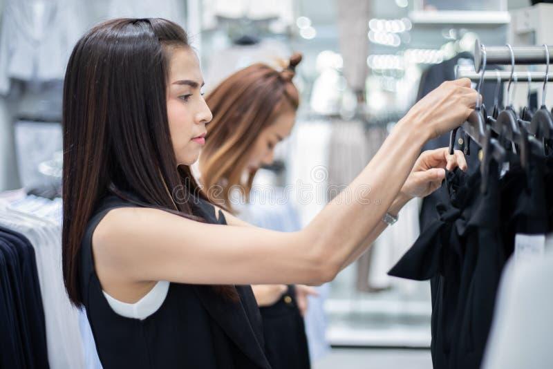 Le asiat f?r ung kvinna tv? med shopping och att k?pa p? gallerian/supermarket/marknaden fotografering för bildbyråer