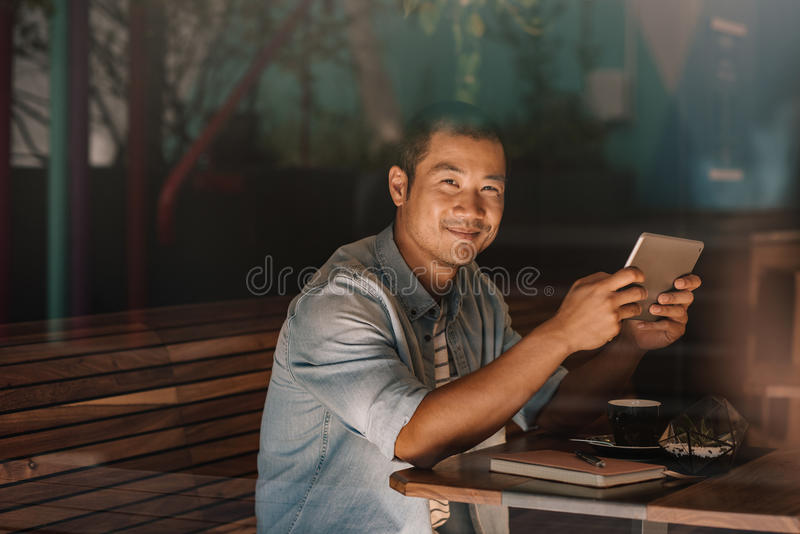 Le asiatiskt bläddra för man som är online-, medan sitta i ett kafé royaltyfri fotografi