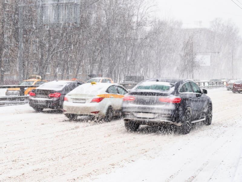 Le automobili guidano alla strada urbana innevata nella bufera di neve immagine stock libera da diritti