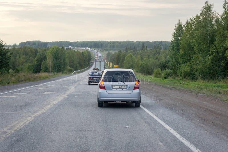 Le automobili guidano lungo la strada principale dopo una foresta verde nella sera fotografie stock libere da diritti