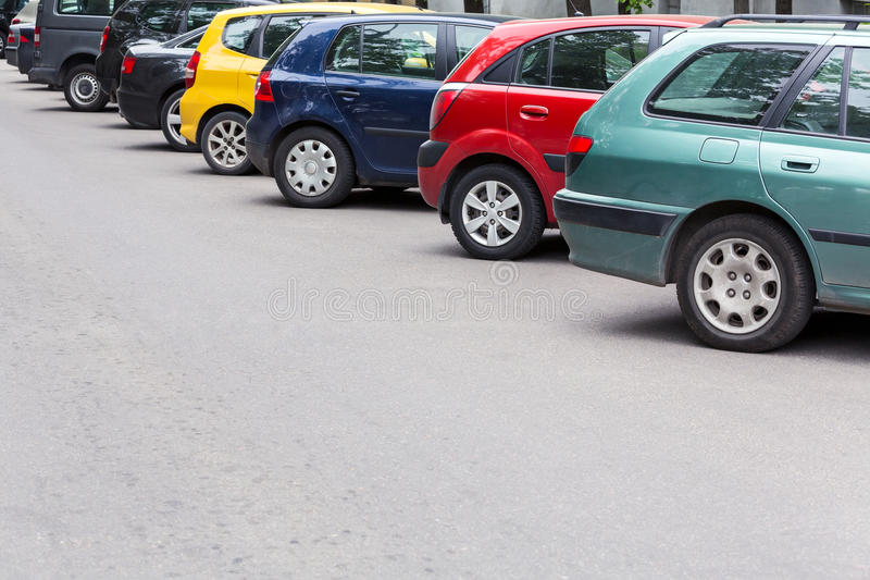 Le automobili multicolori hanno parcheggiato diagonalmente al parcheggio nella via immagine stock libera da diritti