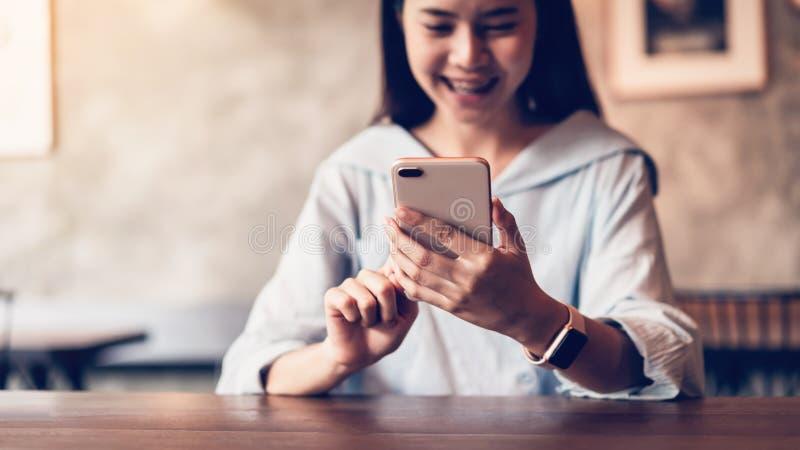 Le av den asiatiska kvinnan som anv?nder smartphonen som smsar p? kaf?t kopieringsutrymme f?r annonser arkivbild