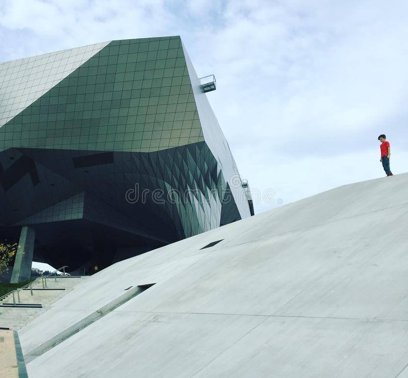 Le bâtiment à angles moderne en verre et en métal avec la pente concrète et la chemise rouge figurent photo stock