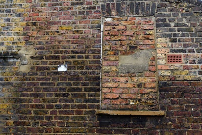 Le bâtiment âgé avec la brique a couvert la fenêtre aveugle images stock