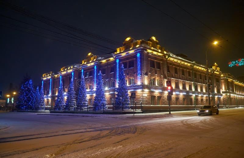 Le bâtiment administratif, l'ancien gymnase masculin classique provincial a habillé des lumières de Noël à Tomsk photographie stock libre de droits