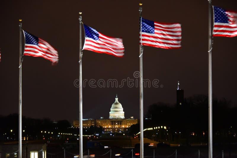 Le bâtiment capitale des USA avec les USA marque le vol image stock