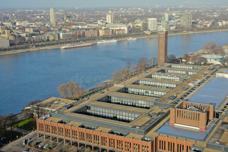Le bâtiment de foire commerciale de Cologne et le ` de Messeturm de ` dominent le long de la rivière le Rhin photos stock
