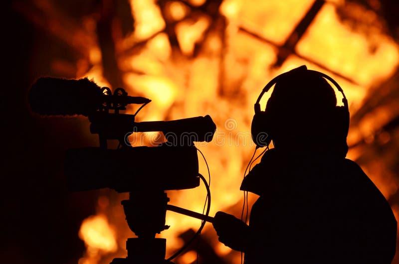 Le bâtiment de pelliculage de journaliste de journaliste de cameraman sur le feu flambe image libre de droits