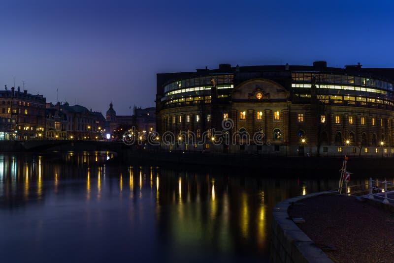 Le bâtiment suédois du Parlement se reflétant dans l'eau au coucher du soleil en hiver à Stockholm photos stock