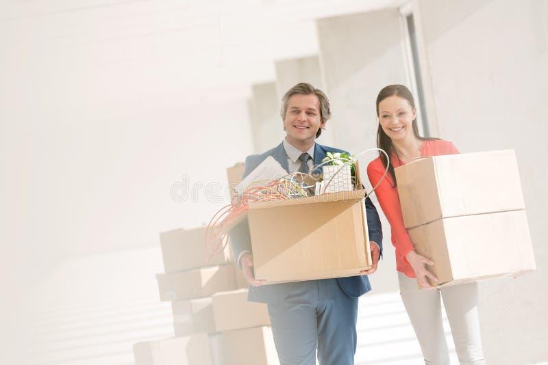 Le bärande kartonger för affärsman och för affärskvinna i nytt kontor royaltyfri fotografi