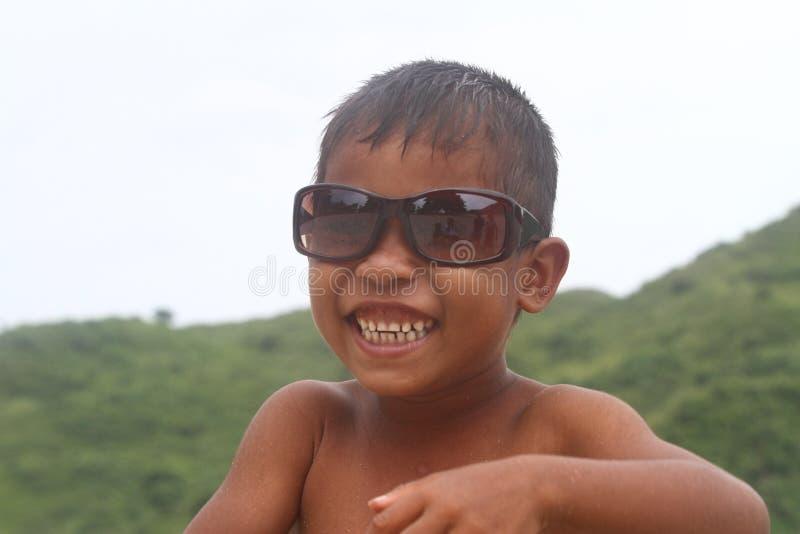 Le bärande solexponeringsglas för asiatisk pojke royaltyfria foton
