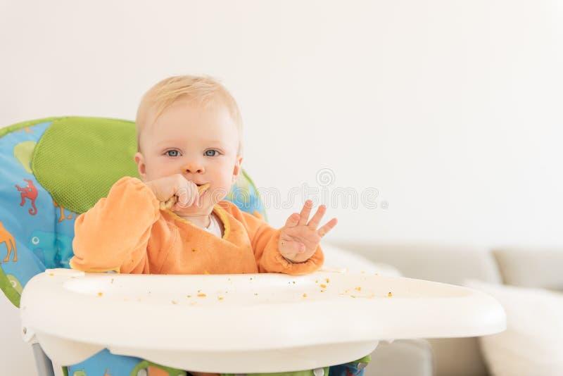 Le bébé adorable avec des yeux bleus se reposant dans le highchair et prennent le déjeuner image stock