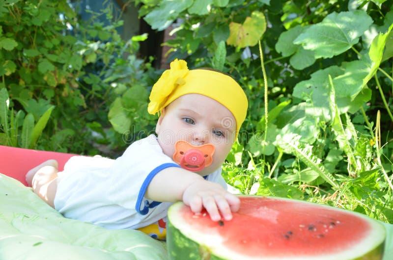 Le bébé adorable mignon d'yeux bleus 6 mois sort la moitié d'une pastèque sur le fond du feuillage Jour ensoleillé image stock