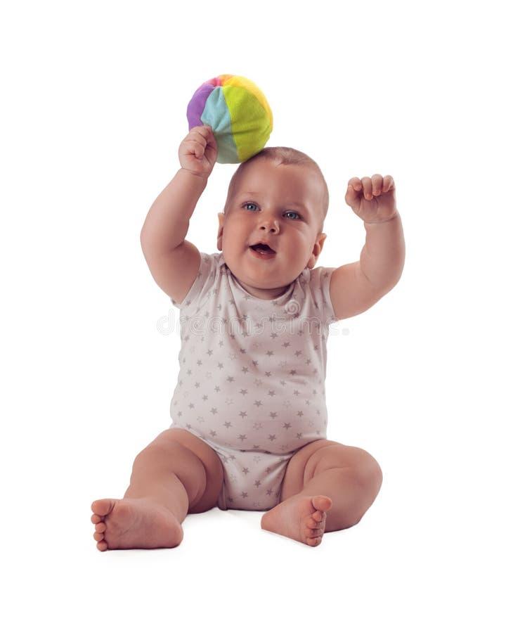 Le bébé adorable a soulevé la boule au-dessus de sa tête D'isolement sur le fond blanc photos stock