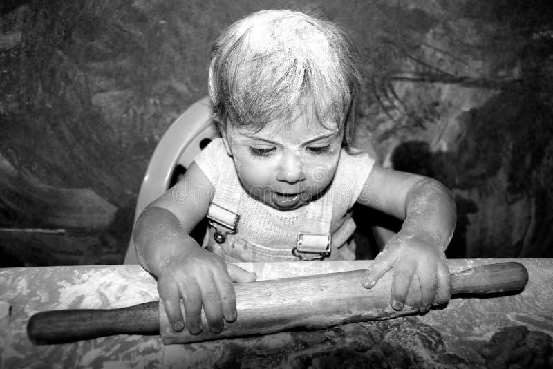le bébé apprend à faire cuire des biscuits de Pâques images libres de droits