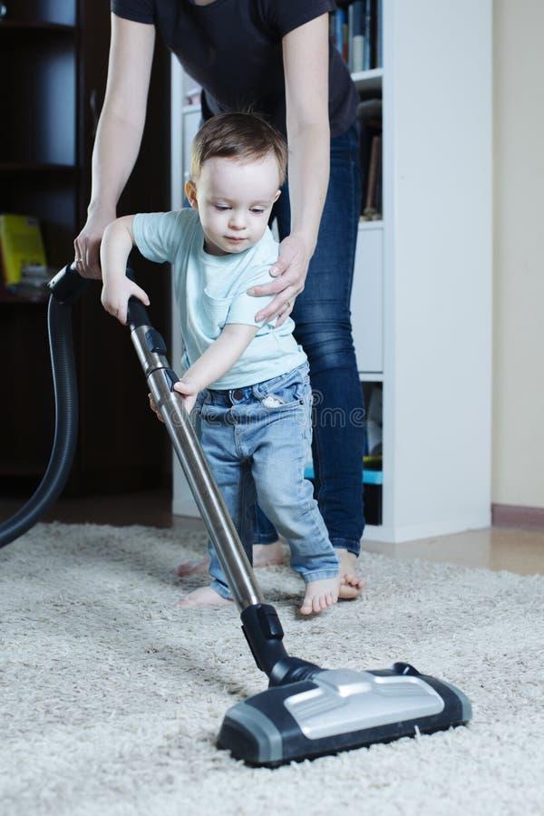 Le bébé apprend à nettoyer à l'aspirateur le tapis dans la chambre avec sa mère photos stock