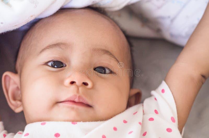 Le bébé asiatique mignon sous une couverture dans le lit après se réveillent photos libres de droits