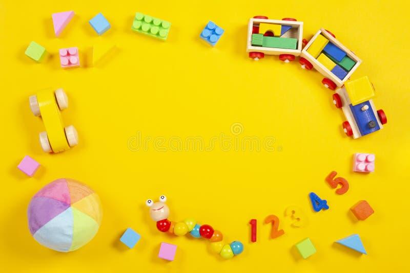Le bébé badine le fond de jouets Train en bois, voiture, cubes colorés et nombres sur le fond jaune photographie stock