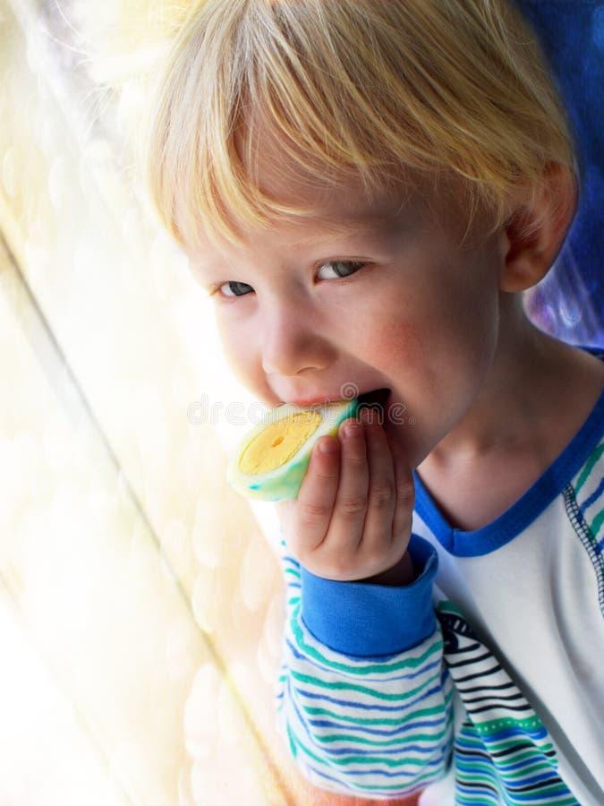 Le bébé blond mord l'oeuf de pâques pour le petit déjeuner photographie stock