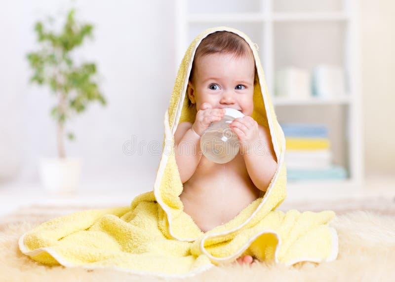 Le bébé boit l'eau de la bouteille enveloppée en serviette photos libres de droits