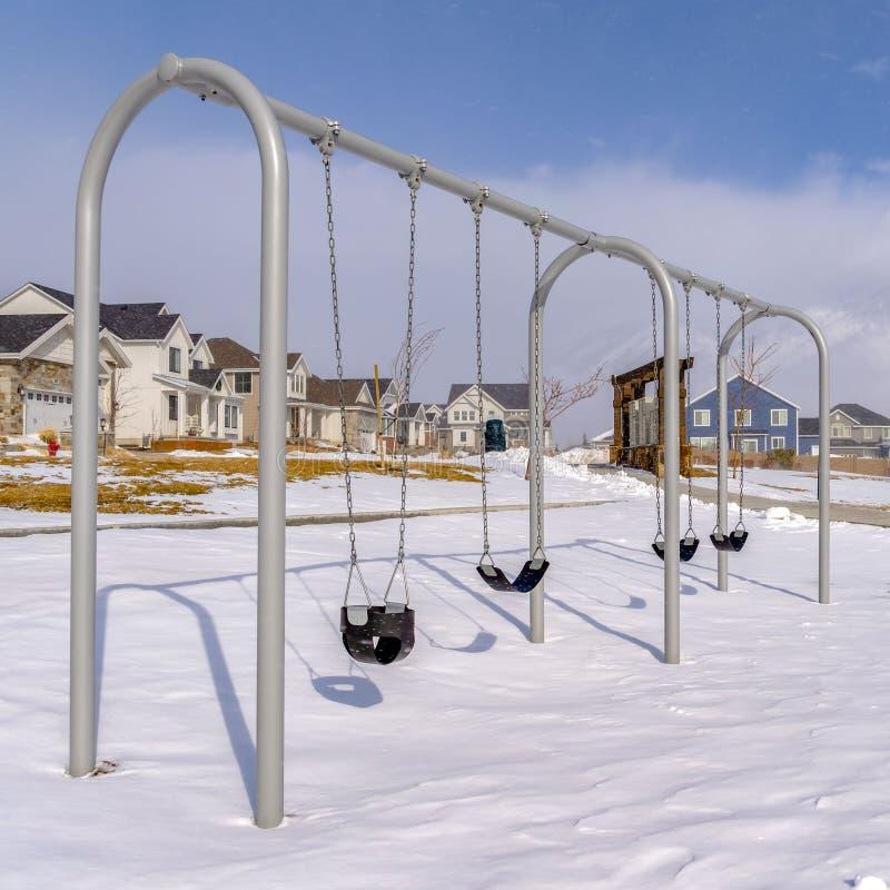 Le bébé carré balance à un terrain de jeu couvert avec la neige propre un jour ensoleillé d'hiver photos libres de droits