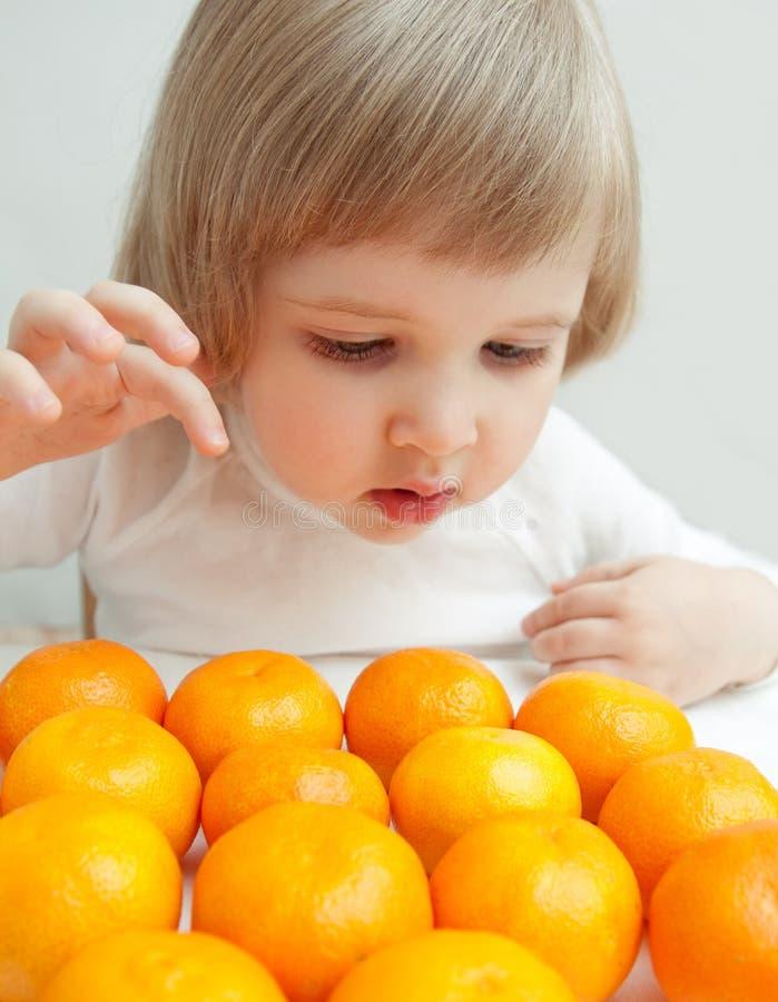 Le bébé choisit une mandarine photo stock