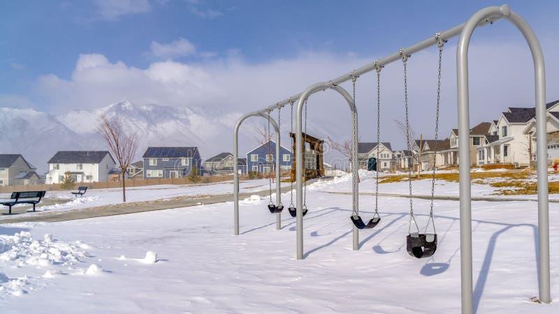 Le bébé clair de panorama balance à un terrain de jeu couvert avec la neige propre un jour ensoleillé d'hiver image stock