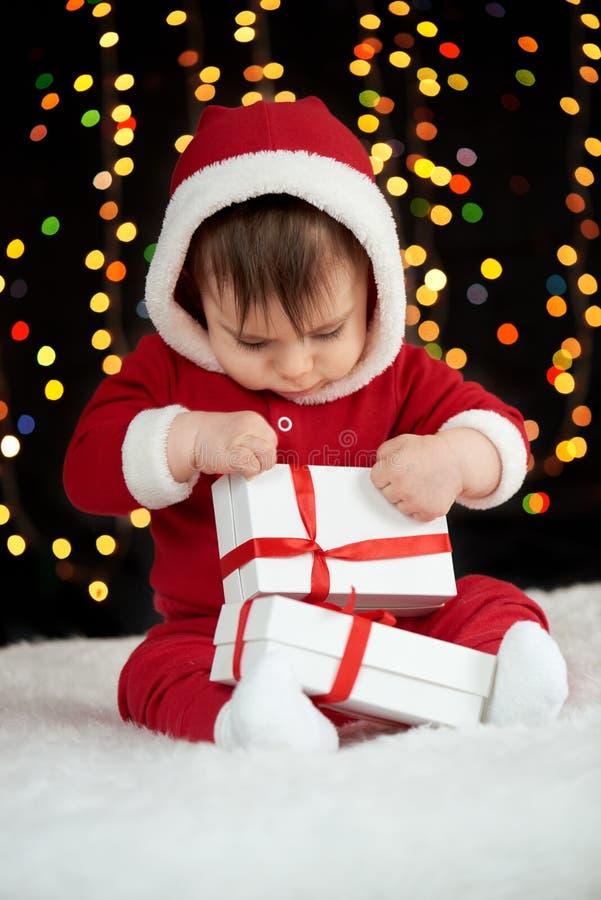 Le bébé déballent des boîte-cadeau avec la décoration de Noël, habillée comme Santa, des lumières de boke sur le fond foncé, conc images stock