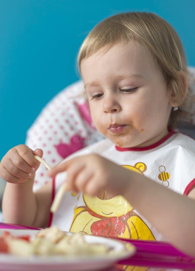 Le bébé déjeune des tomates avec du pain photo libre de droits