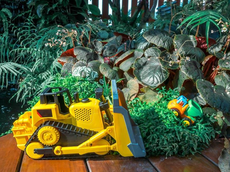 Le bébé d'enfants joue le tracteur et le camion sur le plancher en bois dans le terrain de jeu image libre de droits