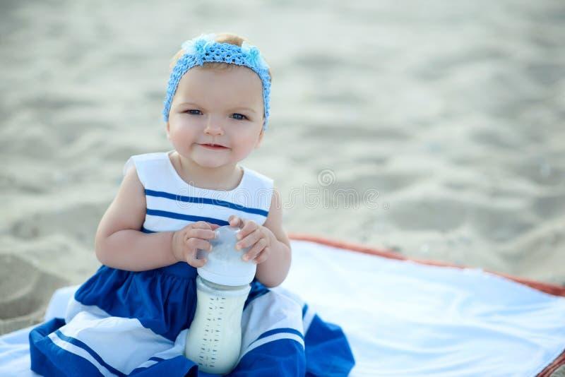 Le bébé d'ute de ¡ de Ð dans la robe rayée intéressante et le bandeau bleu se reposant sur le sable et essayant d'ouvrir une bout image stock