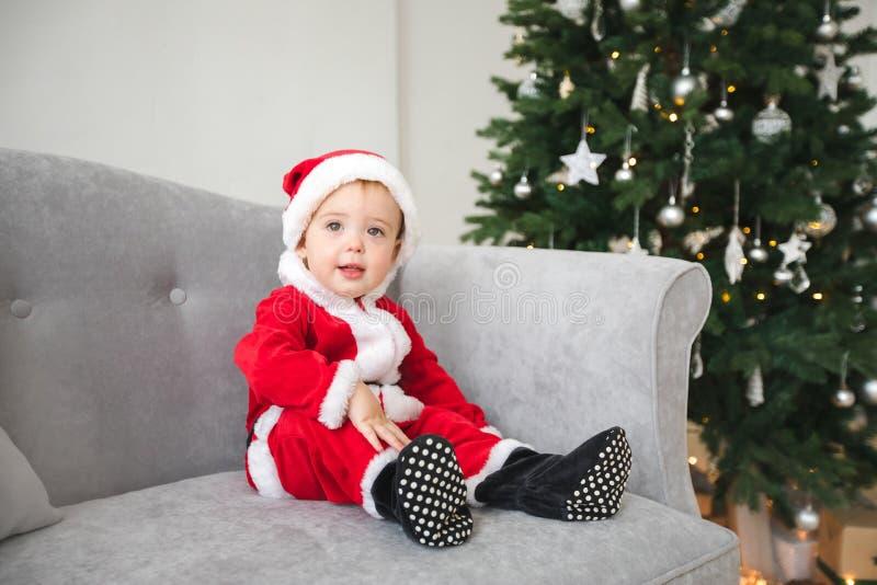Le bébé dans le costume de Santa s'asseyent sur le sofa avec l'arbre de Noël photo libre de droits