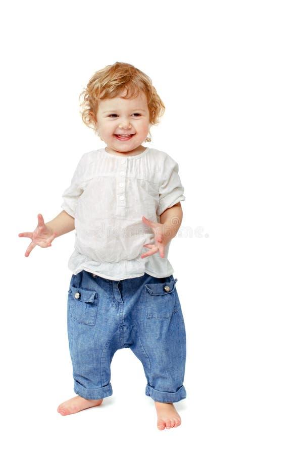 Le bébé de deux ans est heureux et tourne les poignets photos libres de droits