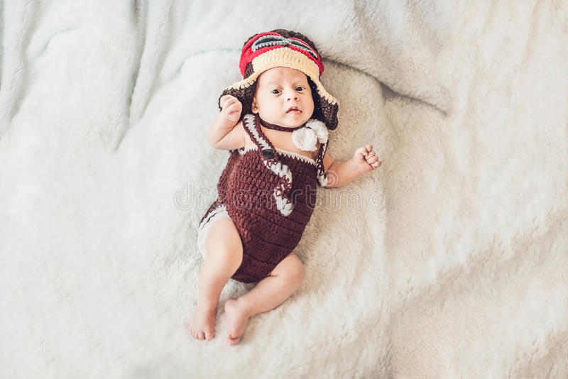 Le bébé de sourire mignon dans le chapeau du pilote vole sur un b blanc photographie stock