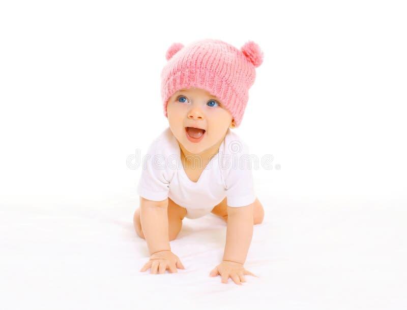 Le bébé de sourire mignon heureux dans le chapeau rose tricoté rampe sur un blanc images libres de droits