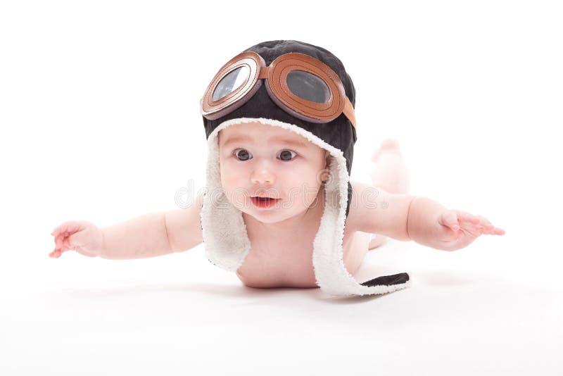 Le bébé de sourire mignon nu dans le chapeau du pilote vole sur W photographie stock libre de droits