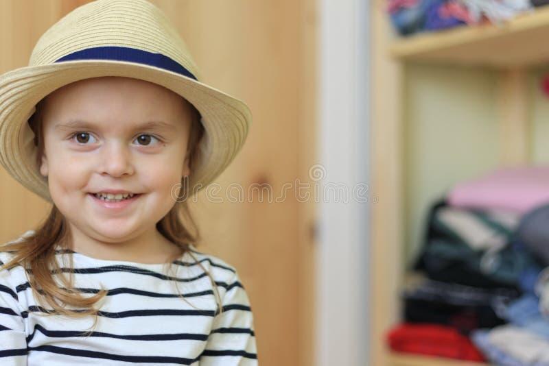Le bébé drôle met sur le chapeau à la maison photos stock