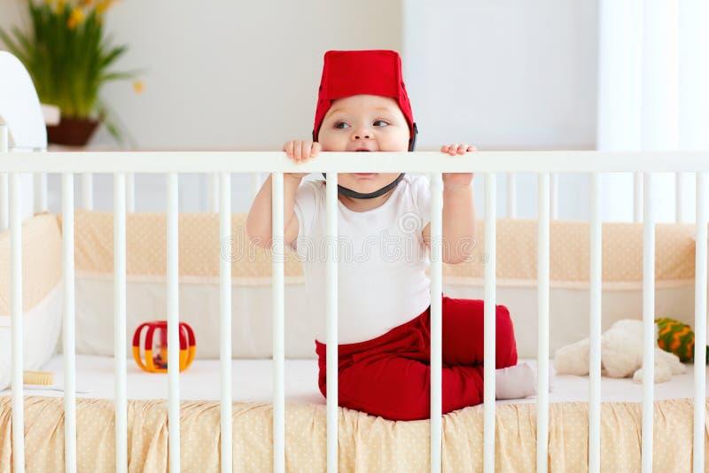 Le bébé drôle mord son berceau pendant que des dents sont piquées images libres de droits