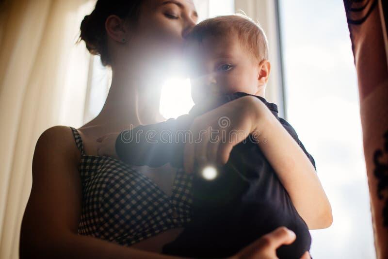 Le bébé est dans des ses bras du ` s de mère images libres de droits